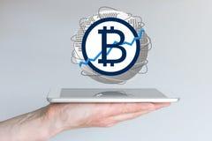 Aumento do conceito global da taxa de câmbio da moeda do bitcoin com a mão que guarda a tabuleta Foto de Stock