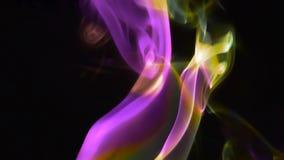 Aumento porpora e giallo del fumo contro un fondo nero stock footage