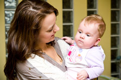 Aunt with baby girl. Pretty young woman (aunt) holding a baby girl on hand Stock Photos