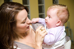 Aunt with baby girl. Pretty young woman (aunt) holding a baby girl on hand Royalty Free Stock Image