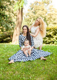 Aunt, mother and baby girl relaxing at park Stock Photos
