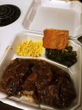 Aunt T's Savoury Oxtails with Brown, Corn, Mustard Greens, an T's Signature Cornbread royalty free stock photo