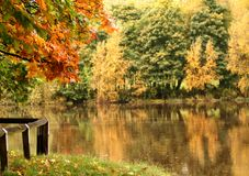 Auntumn embankment. Beautifl Colours with soft focus on flowing River in Background royalty free stock photography