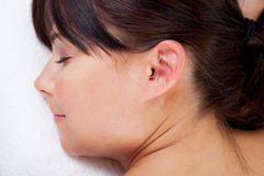 Aurical Acupuncture Treatment. Attractive female relaxing while receiving an acupuncture treatmant on the ear Stock Image