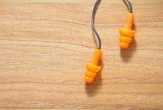 Auricular anaranjado para el ruido de la protección para la seguridad en el backgroun de madera Foto de archivo libre de regalías