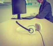 Auricular blanco con la mujer creativa joven que se sienta y que sonríe Imagen de archivo
