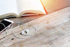 Auricular blanco de la forma del corazón con smartphone y libro abierto en la opinión de sobremesa de trabajo con el espacio de l Imagenes de archivo