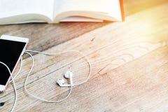Auricular blanco de la forma del corazón con smartphone y libro abierto en la opinión de sobremesa de trabajo con el espacio de l Fotografía de archivo