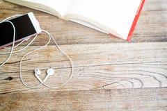 Auricular blanco de la forma del corazón con smartphone y libro abierto en la opinión de sobremesa de trabajo con el espacio de l Fotos de archivo libres de regalías