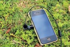Auricular de IPhone 4s Sony con el fondo de la naturaleza Foto de archivo
