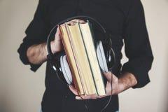 Auricular de la mano del hombre con los libros fotografía de archivo