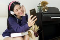 Auricular del adolescente precioso y smartphone el sostenerse que llevan Imagen de archivo