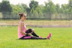 Auricular del smartphone de la hierba de la muchacha del atleta de la vista que se sienta lateral Fotografía de archivo