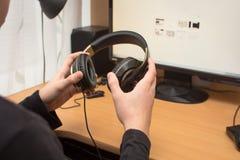 Auricular en muchacho de las manos Fotografía de archivo libre de regalías