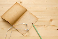 Auricular, libro viejo y lápiz en la tabla de madera Fotos de archivo