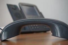 Auricular oscuro (receptor) con un teléfono de la línea horizonte del negocio corporativo en el fondo Foto de archivo