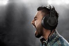 Auricular que lleva de la música del hombre que escucha imagen de archivo