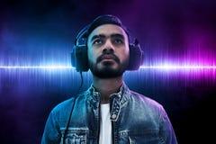 Auricular que lleva de la música del hombre que escucha asiático foto de archivo