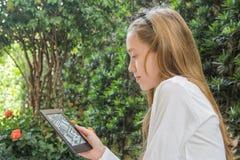 Auricular que lleva de la muchacha del adolescente que juega en la tableta Fotografía de archivo