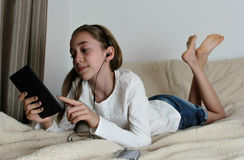 Auricular que lleva de la muchacha del adolescente que juega en la tableta Imagen de archivo libre de regalías