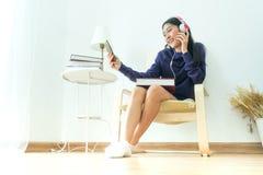 Auricular que lleva del adolescente asiático en sala de estar moderna Fotografía de archivo