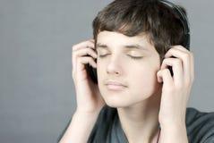 Auriculares adolescentes de los asimientos a los oídos con los ojos cerrados Imagenes de archivo