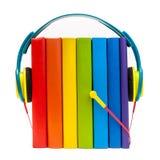 Auriculares alrededor de los libros multicolores del arco iris aislados en un fondo blanco, concepto de los audiolibros Fotos de archivo libres de regalías