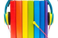 Auriculares alrededor de los libros multicolores del arco iris aislados en un fondo blanco, concepto de los audiolibros Fotografía de archivo libre de regalías
