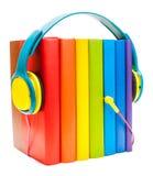 Auriculares alrededor de los libros multicolores del arco iris aislados en un fondo blanco, concepto de los audiolibros Imagenes de archivo