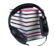 Auriculares audios en una pila de libros con las cubiertas del color. Fotos de archivo