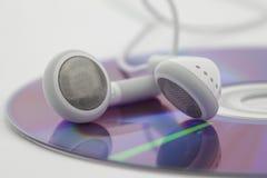 Auriculares blancos en el Cd Imagen de archivo libre de regalías