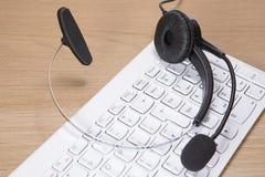 Auriculares com o microfone que encontra-se em um teclado branco Imagens de Stock