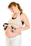 Auriculares de la explotación agrícola de la mujer embarazada en su panza Foto de archivo