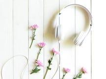 Auriculares de la visión superior en el escritorio blanco con el área rosada de la flor y del copyspace para un texto fotografía de archivo libre de regalías