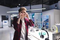 Auriculares de prueba hermosos del hombre joven en la tienda de la electrónica fotografía de archivo libre de regalías