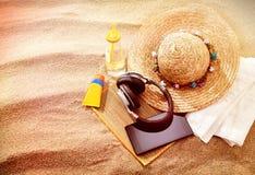 Auriculares del sunhat de la paja y una toalla en una playa Imagenes de archivo