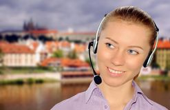 Auriculares desgastando da mulher no escritório; poderia ser a recepção imagens de stock royalty free