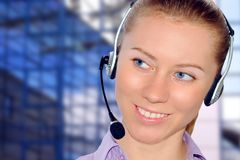Auriculares desgastando da mulher no escritório; poderia ser a recepção imagens de stock