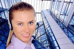 Auriculares desgastando da mulher no escritório; poderia ser a recepção imagem de stock royalty free
