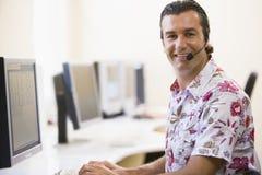 Auriculares desgastando do homem no sorriso do quarto de computador Imagens de Stock