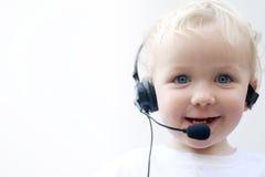 Auriculares desgastando do telefone do menino novo imagem de stock royalty free