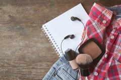 Auriculares determinados de los cosméticos de los vaqueros de la camisa de la juventud y un cuaderno Imagenes de archivo