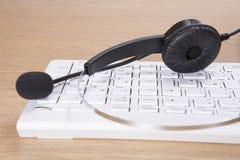 Auriculares e microfone que encontram-se em um teclado de computador Imagem de Stock