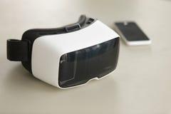 Auriculares e smartphone de VR na mesa, techno do móbil da realidade virtual Fotografia de Stock Royalty Free