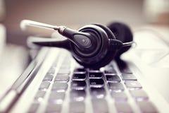 Auriculares em um teclado de laptop Fotografia de Stock