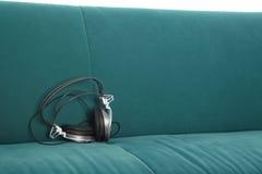 Auriculares en el sofá Imágenes de archivo libres de regalías