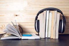 Auriculares en los libros El concepto de audiolibros Fotos de archivo libres de regalías