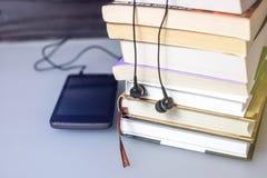Auriculares en los libros El concepto de audiolibros Imagenes de archivo