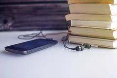 Auriculares en los libros El concepto de audiolibros Foto de archivo