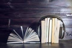 Auriculares en los libros y las notas del vuelo El concepto de audiolibros Imagenes de archivo